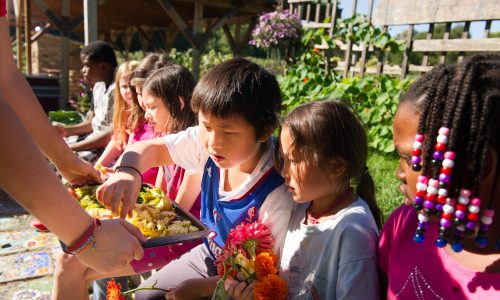 A group of young gardeners share a snack